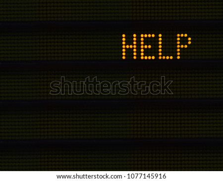 The Word HELP In Orange Lights On A Retro Signboard At An Airport Or Station #1077145916