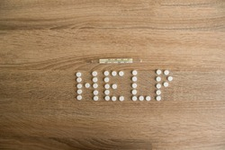 The word help is laid out on a wooden table. The word help with white pills lies on a wooden table.