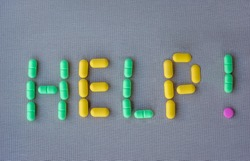 The word HELP made of multi-colored pills on gray textile background