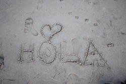 The word hi written in spanish in the sand of the beach with a heart, hola