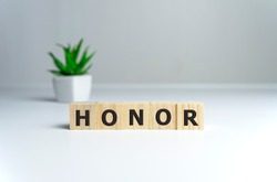 The word Honor written in vintage wooden cubes on a white background