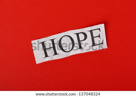 The word HOPE typed out on a scrap of crumpled paper against a red textured paper background