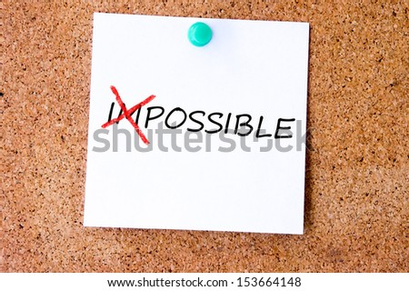 The word Impossible turning into Possible on white sticky note.