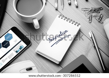 The word innovation and business interface against notepad on desk