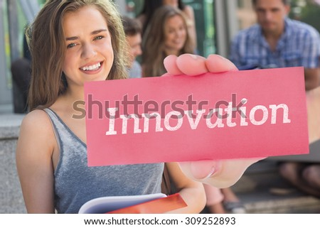 The word innovation and hand showing card against pretty student smiling at camera outside