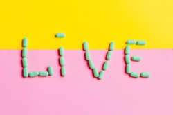 the word is to live. background of two colors. bright words. pills