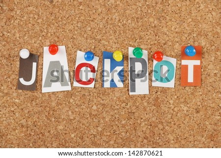 The word Jackpot in cut out magazine letters pinned to a cork notice board. Jackpot is an exclamation for winners at gambling games and is also used to signify achievement