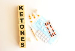The word KETONES is made of wooden cubes on a white background with medical drugs and medical mask.