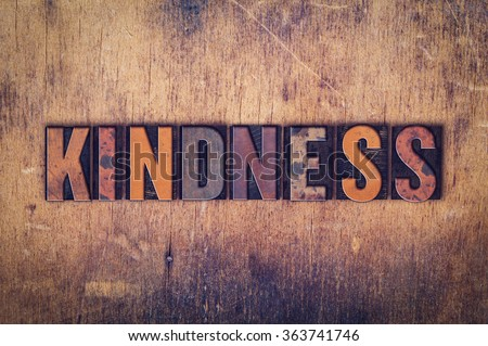 """The word """"Kindness"""" written in dirty vintage letterpress type on a aged wooden background."""