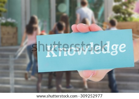 The word knowledge and hand showing card against happy students walking and chatting outside
