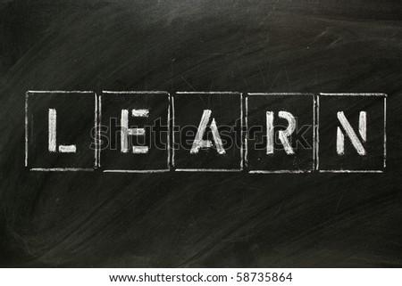 The word LEARN in stencil letters on a blackboard