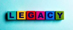 The word LEGACY is written on multicolored bright wooden cubes on a light blue background