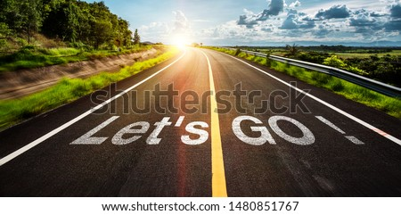 The word let's go written on highway road in the middle of empty asphalt road at  beautiful blue sky.