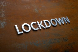 the word lockdown laid with silver metal letters on flat rusted steel sheet background in slanted diagonal perspective