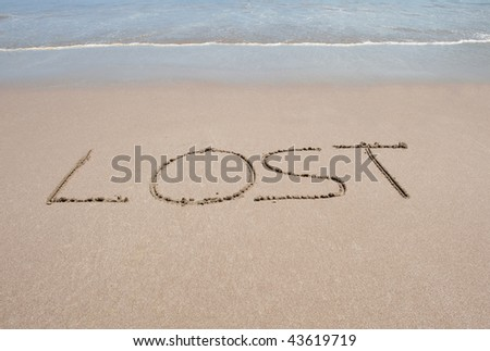 the word lost written in sand on tropical beach near water in big letters