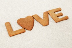 The word Love from biscuits with ginger on sackcloth or rough cloth. Love concept for background. Selective focus and Copy space.