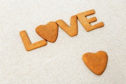 The word Love from homemade cookies with ginger on canvas natural tablecloth. Cookies in heart shape. Selective focus and Copy space.