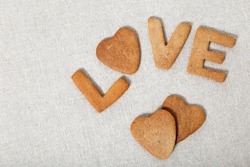 The word Love from homemade cookies with ginger on canvas or cotton material. Cookies in heart shape. Flat lay and Copy space.
