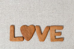 The word Love from homemade shortbread cookies with ginger on linen fabric. Cookies in heart shape. Flat lay and Copy space.