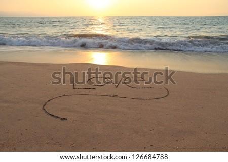 The word Love, handwritten in a sandy beach at sunset.