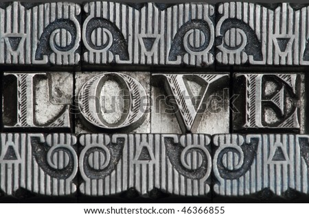 the word love in letterpress type on black background.