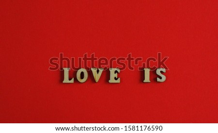 The word Love is against a red background closeup.Valentine's Day background.Valentine's Day card template.