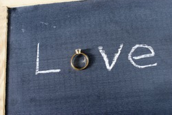 The word love spelled out on a chalkboard with a letter replaced with a diamond ring.