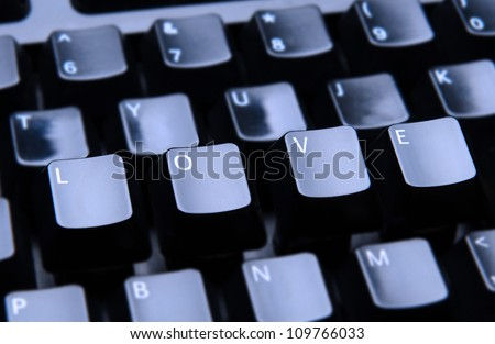 The word Love spelled out on a computer keyboard. Only the keys forming Love are in focus.