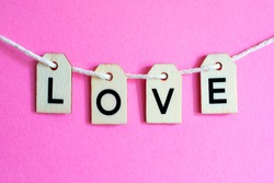 The word LOVE spelt with letter tiles hanging over a pink background.