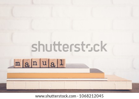 The word Manual, text on wooden cubes on top of books. Background copy space, vintage minimal style. Concepts of help information, Instructions or user guide for education and business products.