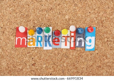 The word Marketing in cut out magazine letters pinned to a cork notice board - stock photo