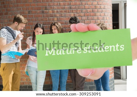 The word mature students and hand showing card against happy students standing and reading