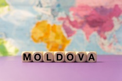 The word Moldova written with wooden dices in front of a purple background and a geographic map