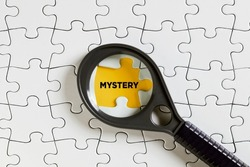 The word mystery on missing puzzle piece with a magnifying glass. To investigate or solve a mystery concept.
