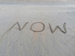The word 'Now' is written in the sand. Is now for the best or are you waiting for a better 'Now', a photo for your current situation.