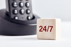 The word 24-7 on wooden block with telephone background. Business concept for customer service, assistance or consultancy availability.