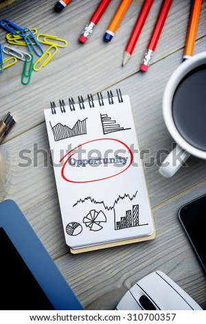 The word opportunity and business graphs against notepad on desk
