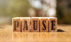 The word pause with wooden blocks on the table in the sunlight.