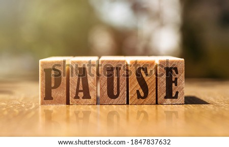 The word pause with wooden blocks on the table in the sunlight. Stock photo ©