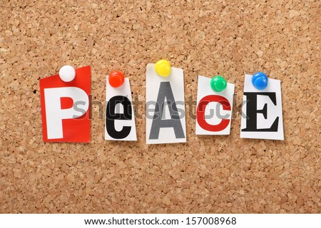 The word Peace in cut out magazine letters pinned to a cork notice board.