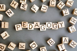 the word pedagogy wooden cubes with burnt letters, correct pedagogy for children, gray background top view, scattered cubes around random letters