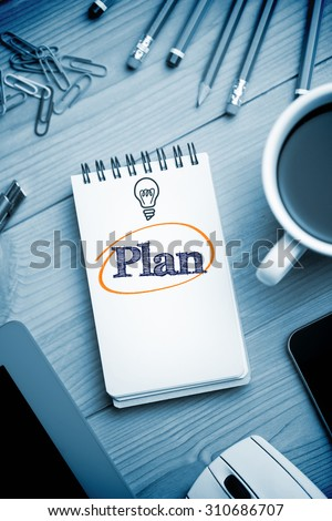 The word plan and currency symbols against notepad on desk