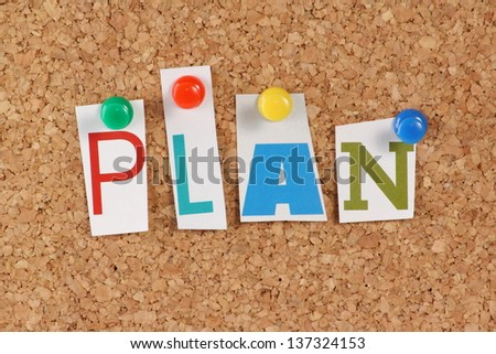 The word Plan in cut out magazine letters pinned to a cork notice board