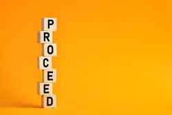 The word proceed on wooden cubes with yellow background. Proceeding in business or law.