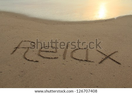 The word relax hand written in the sand at sunset.