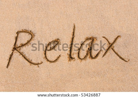 The word RELAX written out on a sandy beach