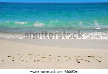 The word resort written in beach sand next to gorgeous ocean water