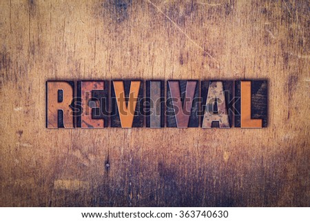 The word 'Revival' written in dirty vintage letterpress type on a aged wooden background. Сток-фото ©