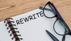 the word REWRITE is written in a notebook with glasses