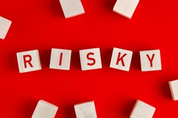 The word risky written on wooden blocks on red background. Concept of risk management or assessment and decision making in an uncertain business environment.
